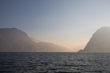 The lake of Lugano with misty sky and mountains at the distance
