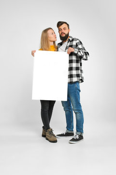 young couple, bearded man and blondie, hugging, holding blank banner, standing still, isolated on white background, Advertisement concept. Mockup for design