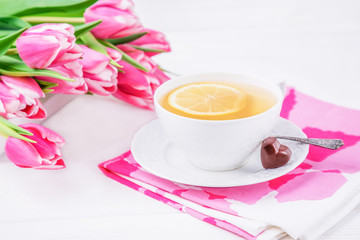 Lemon tea, chocolates heart, pink magenta tulips flowers on white wooden background