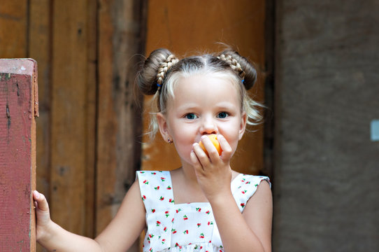 Peach mood! Girls have fun and eat peaches on the porch of a house in the woods.