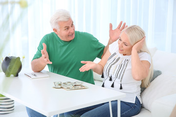 Mature couple with money and piggy bank having argument at table
