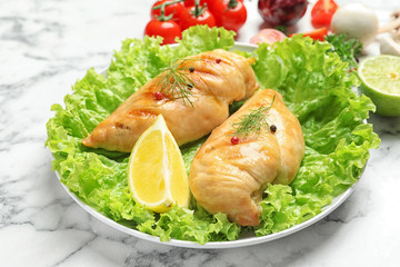 Plate with grilled chicken breasts and garnish on marble table