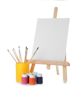 Wooden easel with blank canvas board and painting tools for children on white background