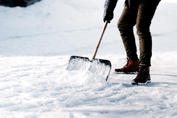 close up of adult cleaning snow from sidewalk and using snow shovel after heavy snowstorm