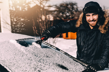 Attractive man cleaning snow off his car - transportation, vehicle and car care concept during winter