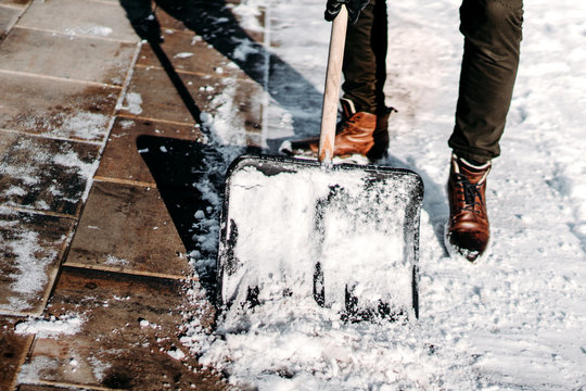 Man with snow shovel cleaning sidewalk during winter time. Close up on snow shovel