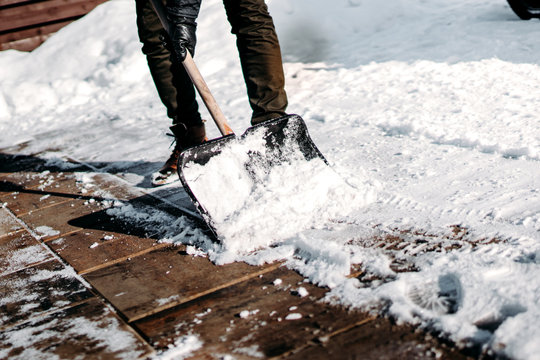 Close up details of working man cleaning out snow from house alley or path using snow shovel