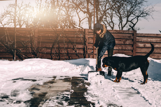 Man removing snow from sidewalk after snowfall. Portrait of man with dog during winter time