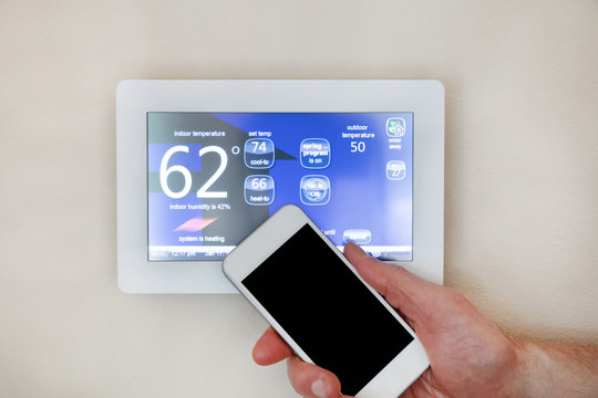 Male hand holding smart phone to operate heating or cooling via digital touch screen thermostat for home