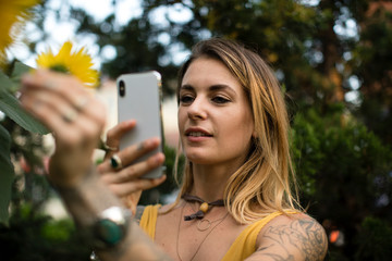 Woman taking a photo of a sunflower
