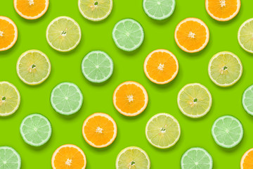 Citrus Fruits pattern on green background. Orange, Lime, Lemon slices background. Flat lay, top view.