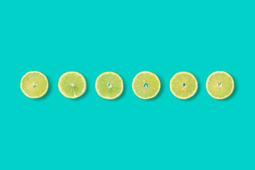 Fruit pattern of lemon slices on blue background. Flat lay, top view, creative summer food concept. Minimal style.