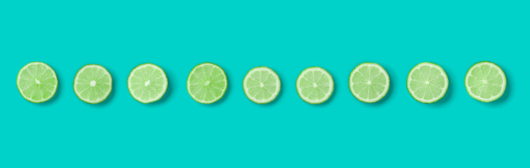 Fruit pattern of lime slices on blue background. Flat lay, top view. Banner, seamless pattern, creative summer food concept.