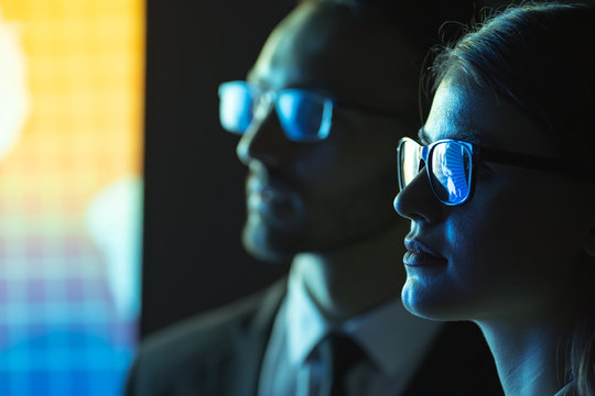The business man and a woman in glasses standing near the screen
