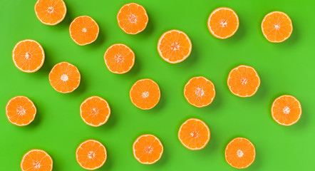 Fruit pattern of fresh orange slices on green background. Flat lay, top view. Pop art design, creative summer concept. Half of citrus in minimal style.