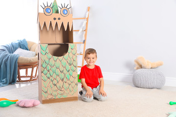 Cute little boy playing with cardboard dragon at home. Space for text