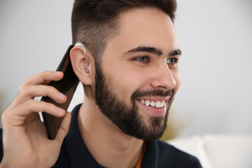 Young man with hearing aid talking on phone indoors
