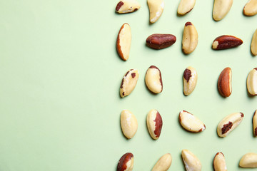 Flat lay composition with Brazil nuts and space for text on color background