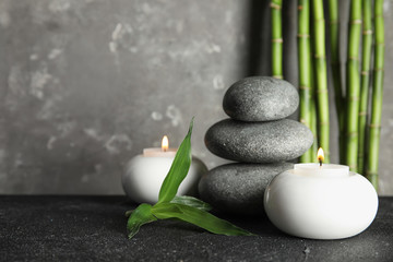 Spa stones with candles and bamboo on table, space for text