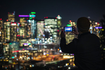 Bright City Lights Bokeh Background to Silhouette of Man Taking Smartphone Photography