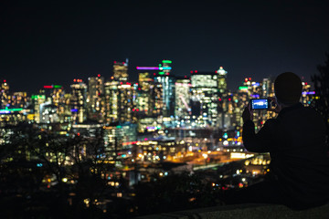 Man Sitting on Ledge Taking Phone Pics of Blurry City Lights Background for Social Media