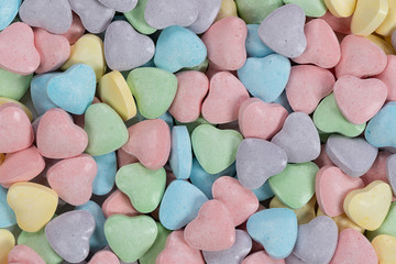 Pastel colored candy hearts macro background