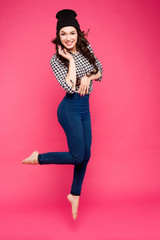 Surprised Fashion model Girl full length jump. Beautiful young woman posing in studio, emotions.
