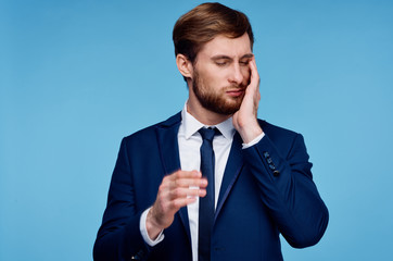 business man holding his cheek on a blue background