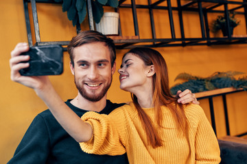 young couple selfie on smartphone cafe
