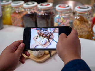 woman using a smartphone photography sweets for social networks in cafe.Focus mobile display while shooting