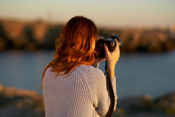 woman takes pictures on camera sunset