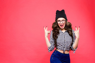 Close up studio portrait of cheerful blonde hipster girl going crazy making funny face and showing her tongue. Pink wall background