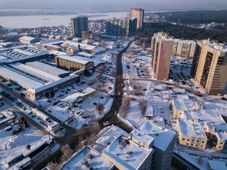 Aerial city view with crossroads, roads, houses, buildings, parks, parking lots, bridges in winter day,  there is a lot of snow around