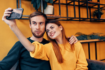 young couple in cafe take selfie on smartphone