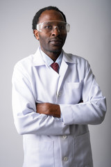 African man doctor wearing protective glasses with arms crossed