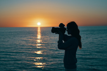 sunset at sea woman photographer with camera