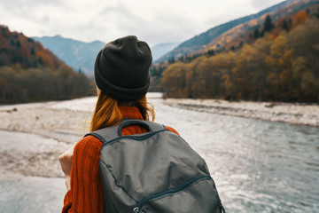 woman with a backpack on the nature of the river