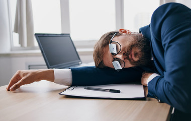 business man in glasses lies on a table with a laptop tired