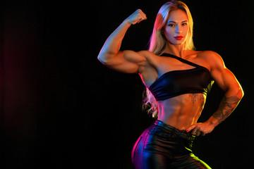 Woman bodybuilder champion athlete, on black background.