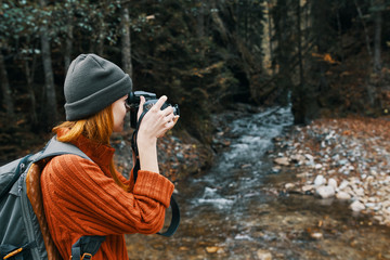 woman takes pictures of nature on camera trip