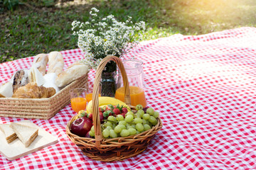 Foto op Aluminium Picknick picnic bread crossiant basket with fruit on red white cloth