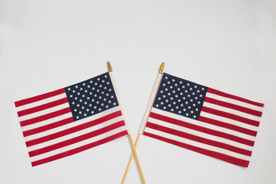 Two American flags crossing each other on white background