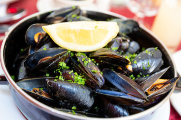 Shallow depth of field image of mussels steamed in white wine with fresh lemon and parsley