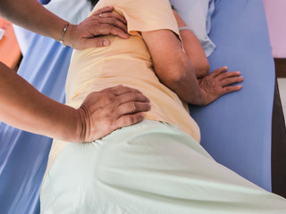 Senior lady having body and legs massage by therapist.