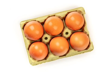 A photo of eggs in a carton, shot from the top on a wooden background with copy space