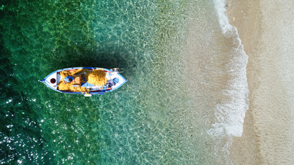Aerial top view photo of beautiful traditional fishing boat from famous small picturesque village of Parga with turquoise crystal clear sea, Ionian, Greece