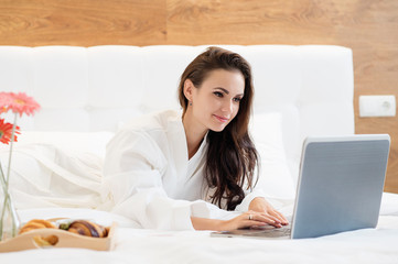 Beautiful young woman dressed in bathrobe lying on bed and working with laptop in hotel room.