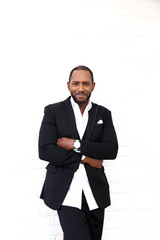 Handsome cheerful african american business man in classy black suit.