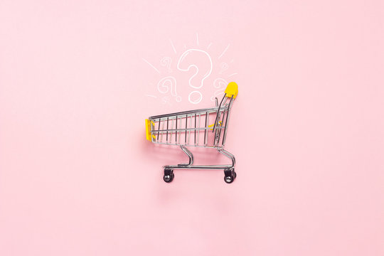 Shopping trolley from the supermarket on an isolated pink background. Shopping in the Mall, shop, shopping, a large selection. Question mark. Flat lay, top view.
