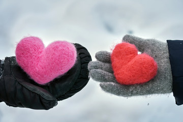 Man and a woman wearing winter gloves giving their woolen hearts to each other on the snow background in winter outdoors. Exchange of hearts. Love, helthcare, devotion,valentine's day concept.